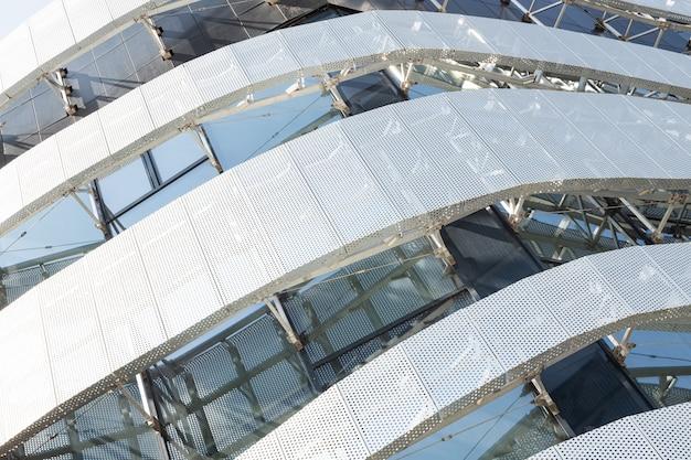 둥근 구멍 및 창 금속 천공 된 패널과 높은 현대적인 건물 건설의 대각선보기. 현대 건물의 코너