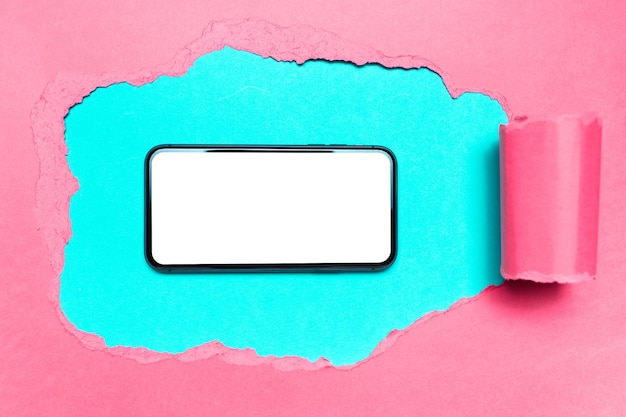 Diagonally torn pink paper, smartphone with mockup in hole on of blue color.
