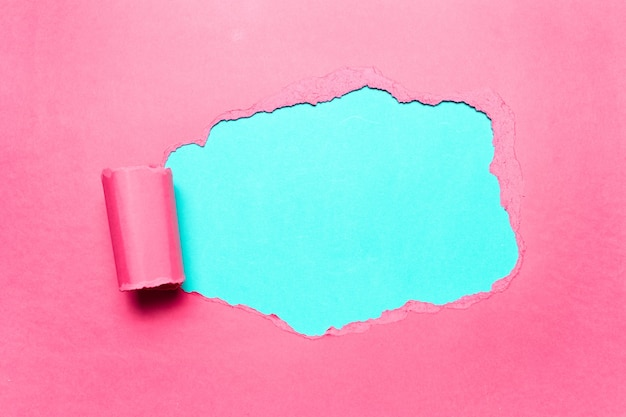 シアンの背景のテキストのための空きスペースで斜めに引き裂かれたピンクの紙。