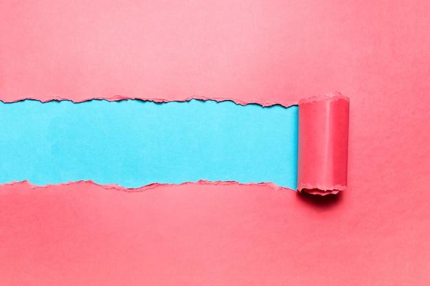 シアンの背景のテキストのためのスペースを持つ斜めに引き裂かれたピンクの紙。