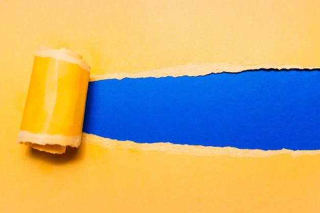 青い背景のテキストのためのスペースを持つ斜めに引き裂かれた黄色い紙。