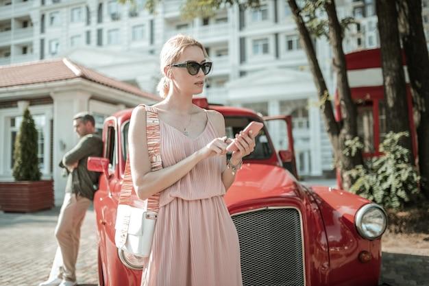 전화 걸기 그녀의 친구에게 전화하려고 그녀의 손에 스마트폰으로 그녀의 남편 앞에 서 있는 아름 다운 여자.
