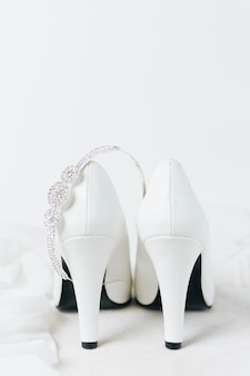 Diamond crown over the pair of white wedding high heels against white backdrop