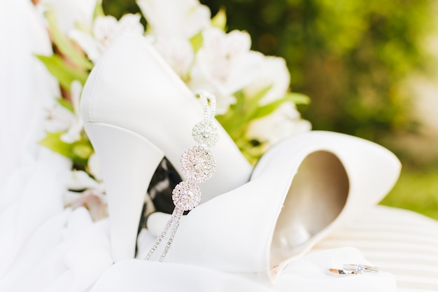 Diamond crown over the pair of white wedding high heels with rings on table