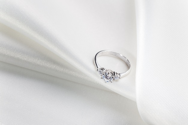 Diamond engagement wedding ring on white fabric