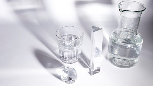 Diamond; glass of water; prism and beaker with shadow on white backdrop
