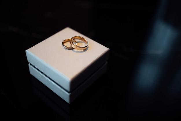 Обручальные кольца из золота с бриллиантами на белой коробке.