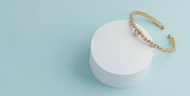 Diamond golden bracelet on white round platform on blue wall with copy space