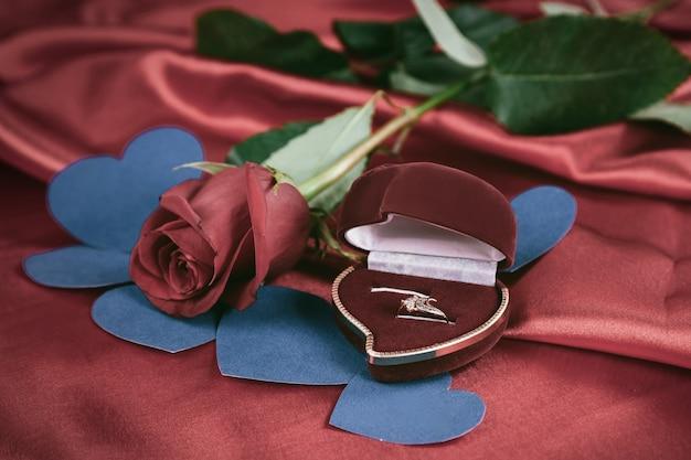 밝은 빨간색 배경에 다이아몬드 반지와 장미