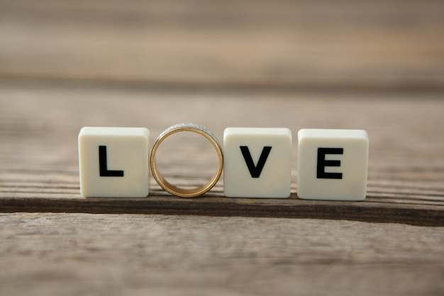 愛のメッセージを表示する白いブロック間のダイヤモンドリング