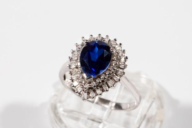 Diamond ring. diamond ring with sapphire on white background. ring with diamonds and large sapphire. golden wedding rings.
