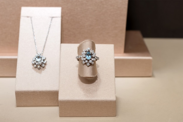 Diamond ring and necklace with blue precious gems. white golden ring on stand. fashion luxury accessories