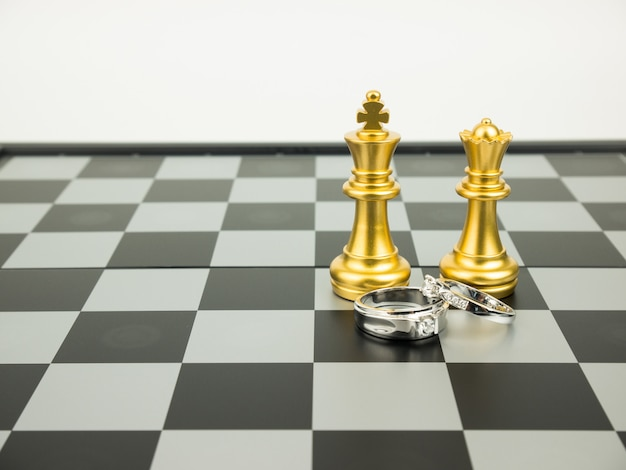 Diamond ring with king and queen chess on the board, wedding concept.