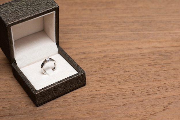 Diamond wedding ring in the box on wooden table.
