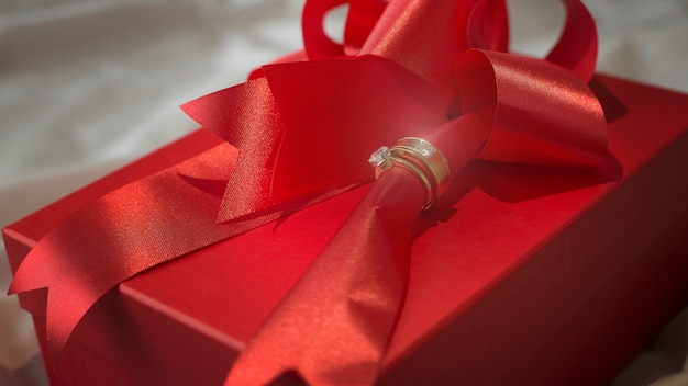 Diamond wedding ring on gift box red ribbon