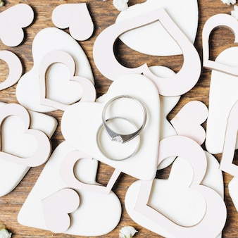 Diamond wedding rings on white heart shapes cut out