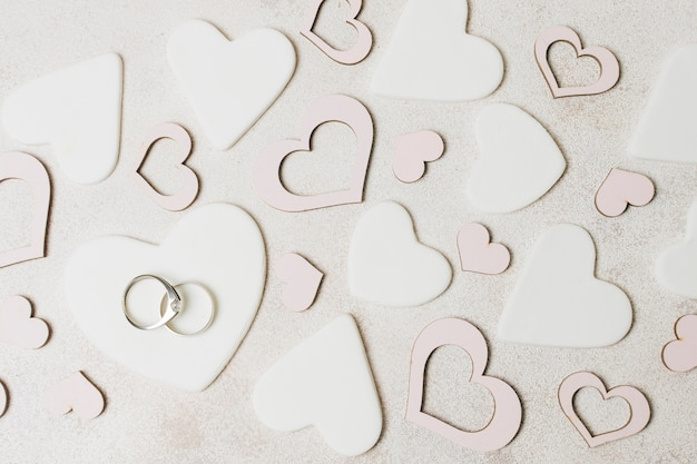 Diamond wedding rings on white and pink heart shape over the concrete backdrop