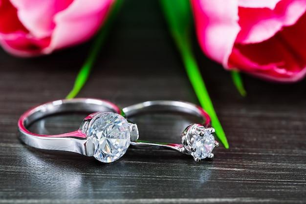 Diamond wedding rings with tulip flower on black