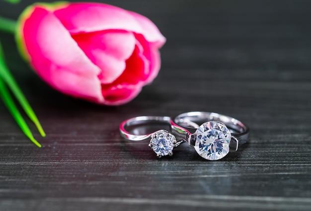 검은 배경에 튤립 꽃과 다이아몬드 결혼 반지