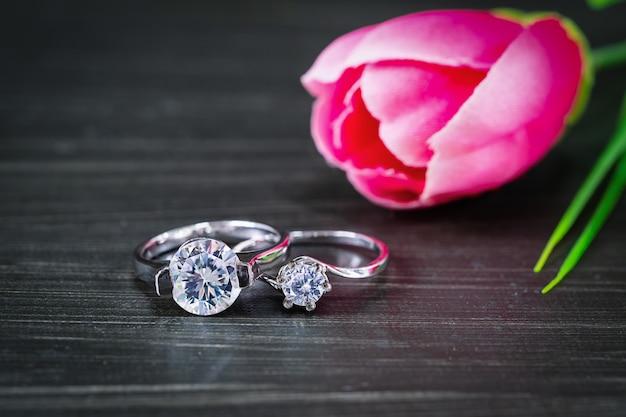 블랙 테이블에 튤립 꽃과 다이아몬드 결혼 반지