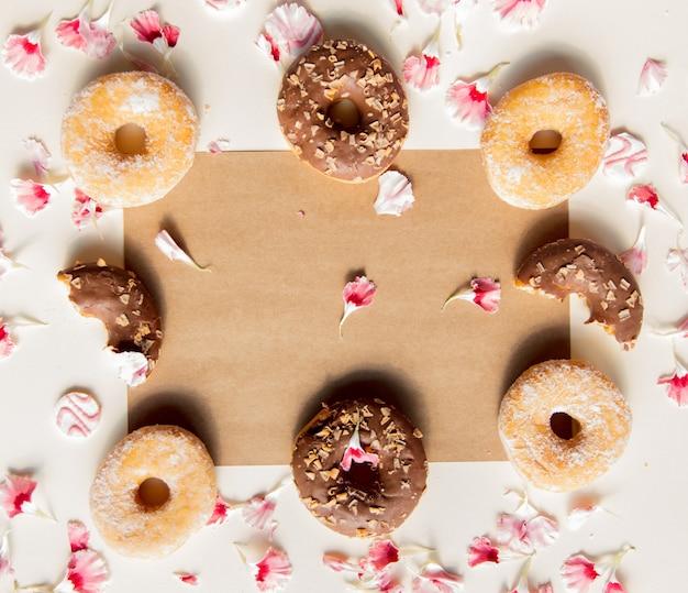 Лепестки диантуса и пончики с естественными тенями на пастельно-желтом фоне. вид сверху