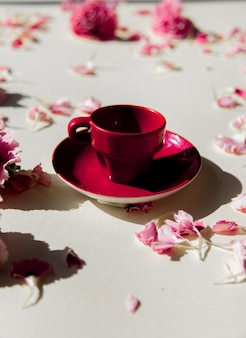Лепестки диантуса и чашка чая с естественными тенями на пастельно-желтой поверхности. вид сверху