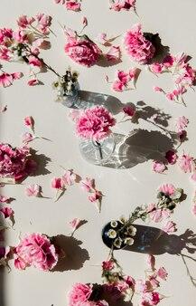 Лепестки диантуса в стакане с естественными тенями на пастельно-желтой поверхности. вид сверху
