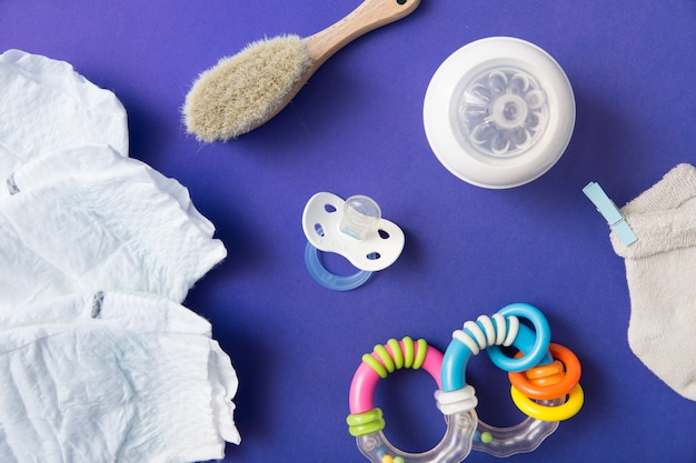 Diaper; brush; pacifier; milk bottle; sock and rattle on blue background