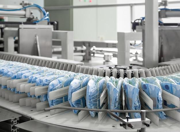 컨베이어 벨트 근접 촬영에 기저귀입니다. 팸퍼스 생산을 위한 공장 및 장비