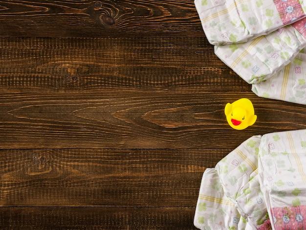 Diapers and rubber duckling on wooden background