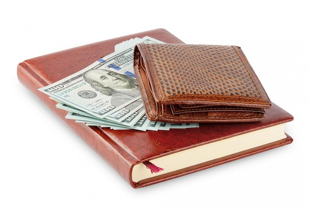 Дневник и коричневый кожаный кошелек с пачкой стодолларовой банкноты