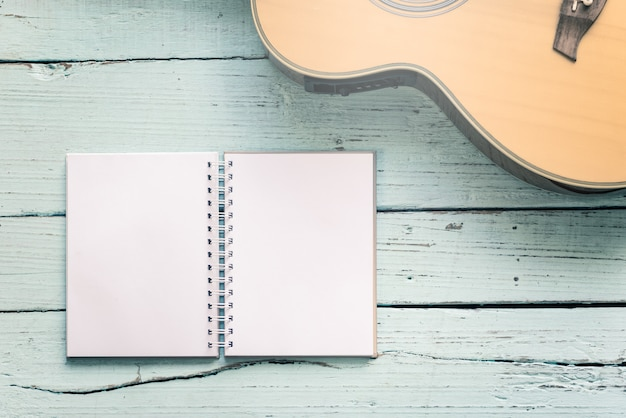 The diary blanks with an acoustic guitar on the wooden table of music composer for musical notes background