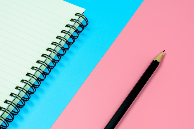 Diary book and a pencil on blue and pink background with copy space.