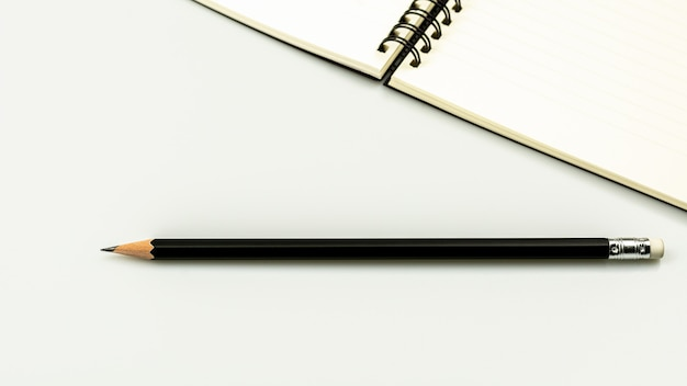 Diary book and a pencil on white desk background with copy space
