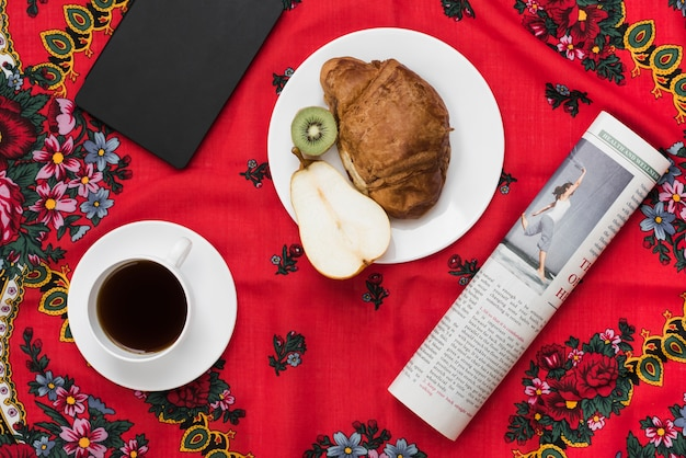 Diary; coffee cup; fruit; croissant and newspaper on red floral tablecloth