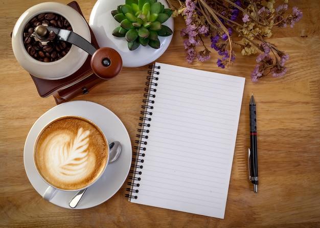 日記、花、木製テーブル上のコーヒーマグ。