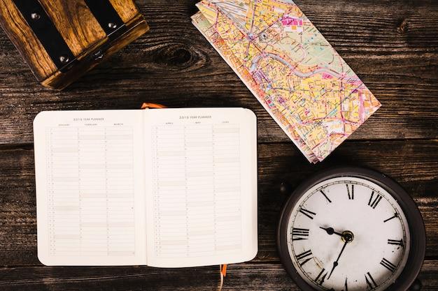 Дневник, карта и часы на деревянной доске