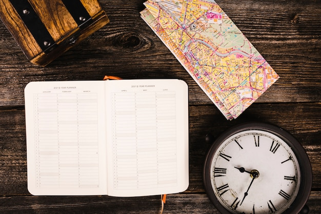 Diary, map and clock on wooden plank