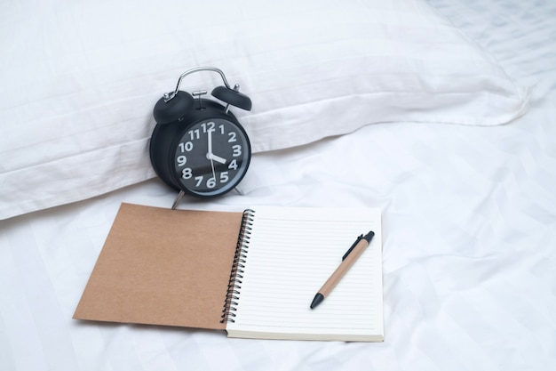 Diary or notebook and vintage alarm clock on bed in bedroom at home or hotel.