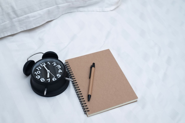 Diary or notebook and vintage alarm clock on bed in bedroom
