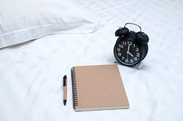 Diary or notebook and vintage alarm clock on bed