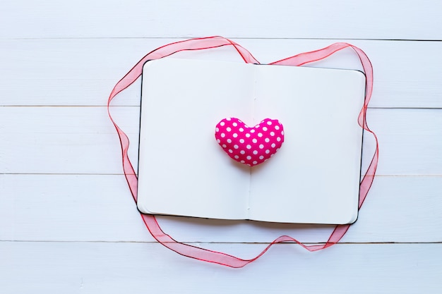 Diary notebook with  valentine's hearts on white wooden background.