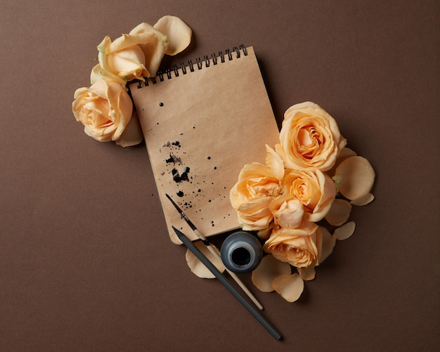 Diary or notebook with yellow roses around, top view