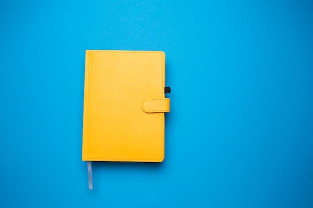 Дневник желтого цвета на синем фоне крупным планом.