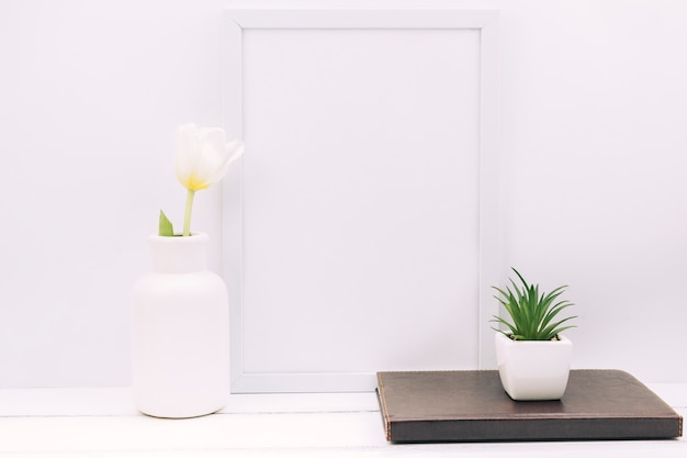 Diary; plant; tulip flower with blank photo frame on white table