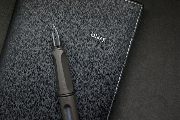 Diary with fountain pen on black background