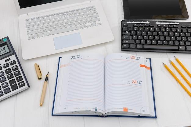 机の上のラップトップ、職場の概念と日記