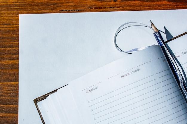 Дневник с ручкой на белой бумаге на столе