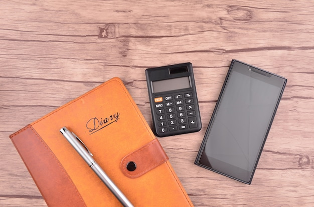 Diary with pen, smart phone, and calculator on wood table