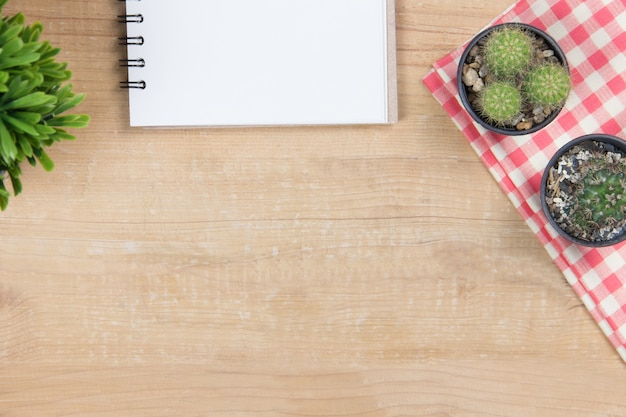 Diary on wooden of brown with cactus on napkin plaid and small tree